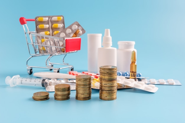 Stacks of coins in a row ascending, shopping trolley cart filled medicinal tablets and pills and scattered drugs