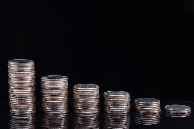Stacks of coins worth going down on black background