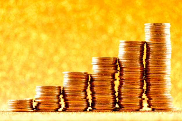 Stacks of copper coins on golden background