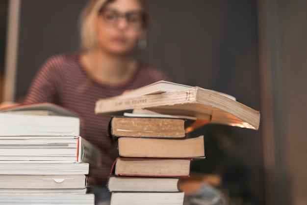 女性の近くの本の積み重ね