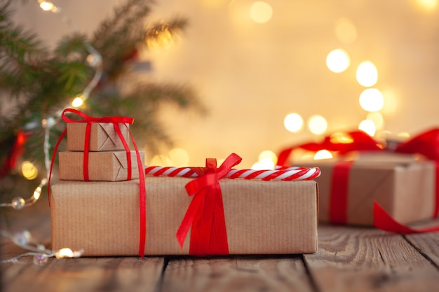 Стопки рождественских подарков под елкой с расфокусированными огнями.