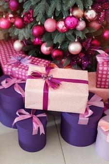 Стеки рождественских подарков под украшенной елкой