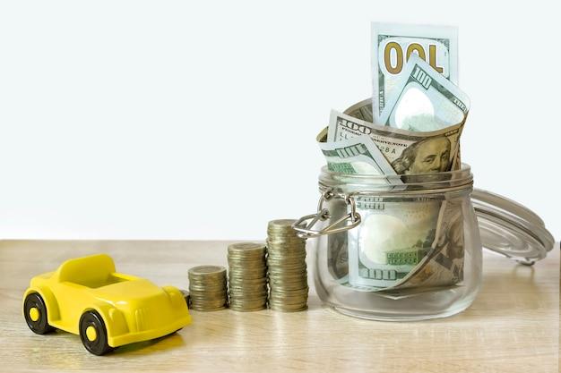 다른 높이의 동전 더미는 경제 성장을 상징하고, 지폐가 있는 유리 은행, 자동차를 절약하는 상징입니다. 돈 개념을 저장합니다. 지속 가능한 개발을 금융.