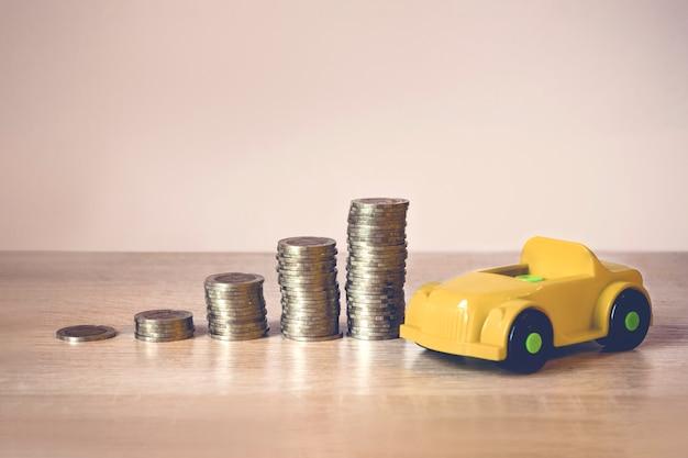다른 높이의 동전 더미는 경제 성장을 상징하고 특정 목적을 위한 절약 개념의 상징인 자동차의 장난감 모델을 상징합니다. 금융, 투자 및 퇴직 계획 개념입니다.