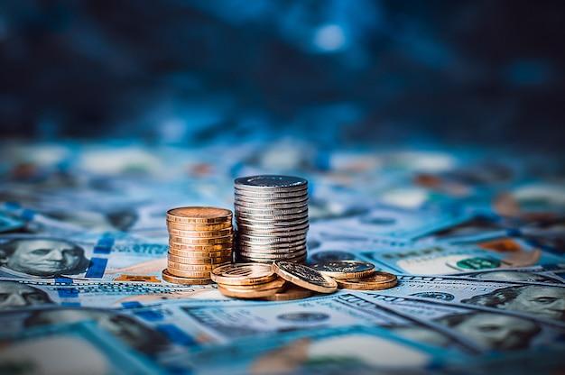 Стопки монет стодолларовых купюр разбросаны по всему пространству. монеты собраны в две колонки, они блестящие, золотистого цвета.