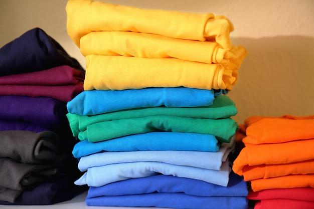 棚に印刷するために準備されたカラフルなtシャツのスタック