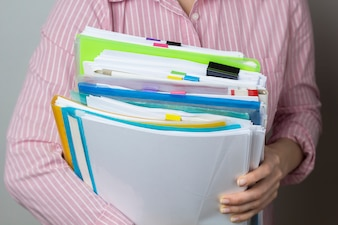 Stacks of documents in paper files in hands, business report documents.