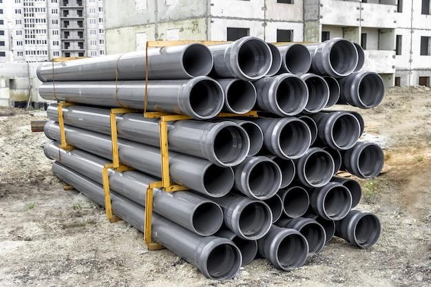 建設現場での灰色のプラスチックパイプのスタック。