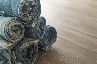 Stacks of jeans clothing on wood