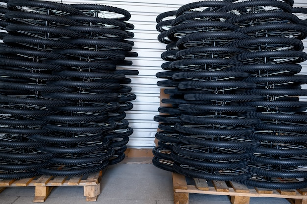 Стопки новых велосипедных колес на поддоне, никто. магазин запчастей для велосипедов на заводе, шины в ангаре, ряды велосипедных дисков и шин