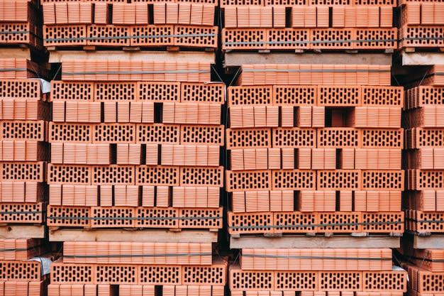 Стеки оранжевого глиняного кирпича на поддоне