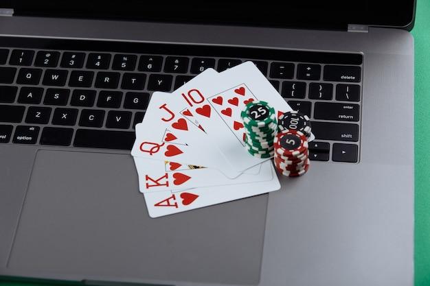 ラップトップコンピューター上のポーカーチップとトランプのスタック。カジノとポーカーのオンラインコンセプト。
