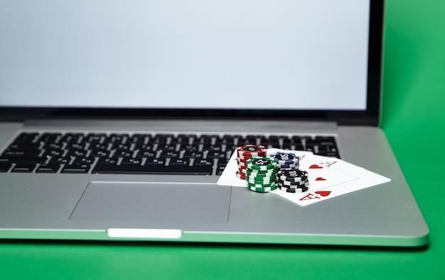 ラップトップコンピューター上のポーカーチップとトランプのスタック。オンラインカジノのコンセプト。