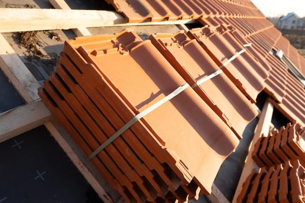 Стеки желтой керамической черепицы для покрытия крыши строящегося жилого дома.