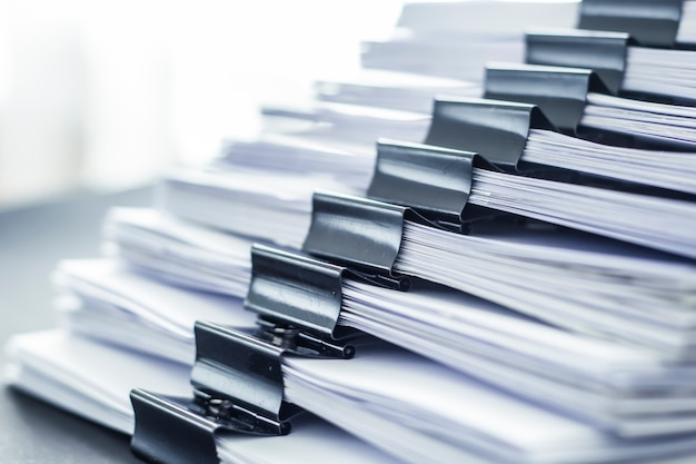 Stacks of office working paper documents files with black clip.