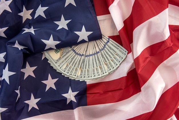 Stacks of the  one hundred dollar bill lying on american flag. save finance concept