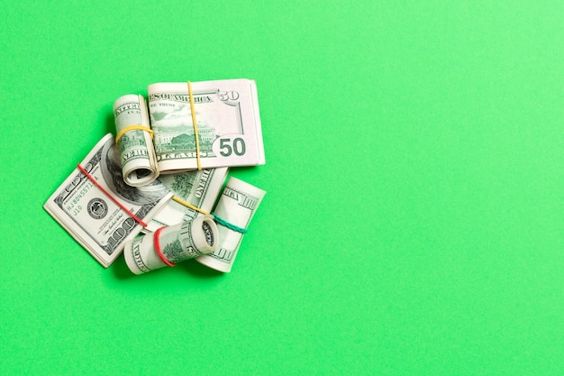 Stacks of one hundred dollars banknotes close-up on colored background business  top view with copyspace