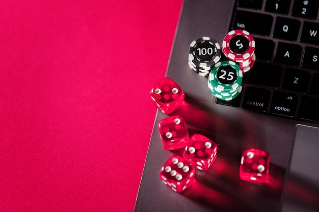 Stacks of poker chips, dices and laptop. poker online concept.
