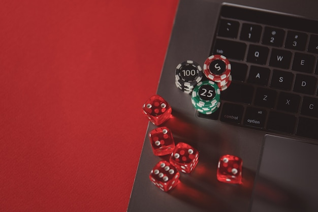 Stacks of poker chips dices and laptop on a red background poker online concept
