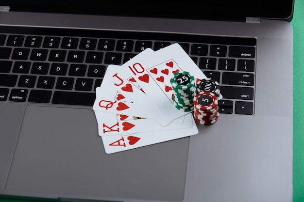 Stacks of poker chips and playing cards on a laptop computer. casino and poker online concept.