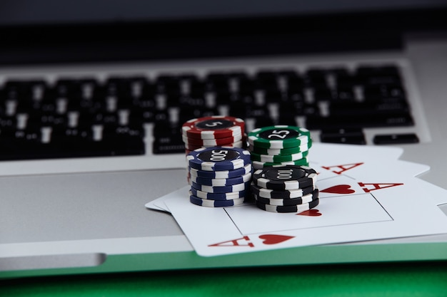Stacks of poker chips and playing cards on a laptop computer. online casino concept.