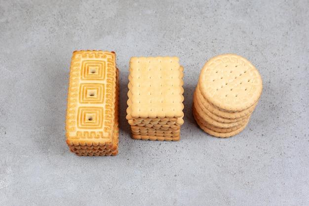 Pile di vari biscotti su sfondo marmo. foto di alta qualità