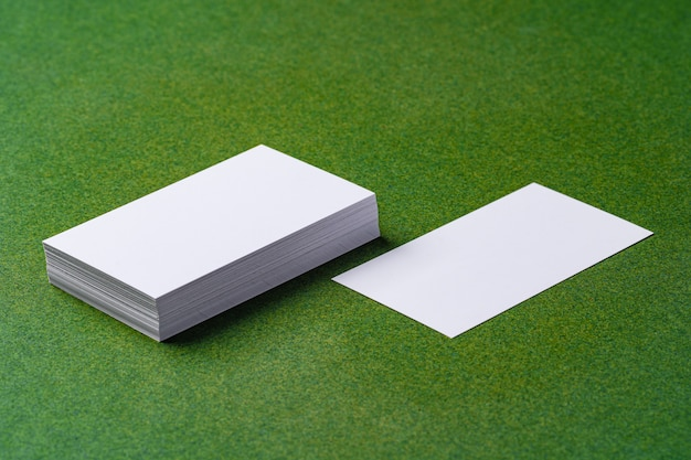 Stacks of white business cards on dark green background