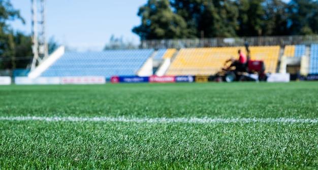 Стадион, арена, футбольное поле. зеленая трава на открытом стадионе, выборочный фокус. спорт и игры. здоровый образ жизни. играть в футбольное поле. сетка с разметкой.