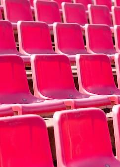 Сиденья стадиона, красного цвета. футбольная, футбольная или бейсбольная стадионная трибуна без болельщиков