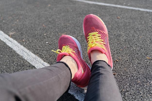 Stadium track background, treadmill female legs in sneakers