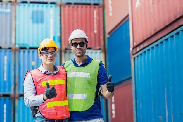 Персонал и прораб контролируют загрузку контейнера, рабочая группа счастлива, наслаждаясь работой, стоя улыбается рука показывает палец вверх.