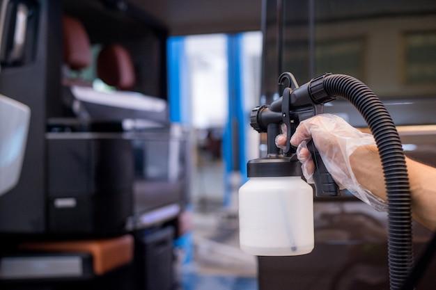 Сотрудники распыляют в машине, чтобы предотвратить вирусы и бактерии.