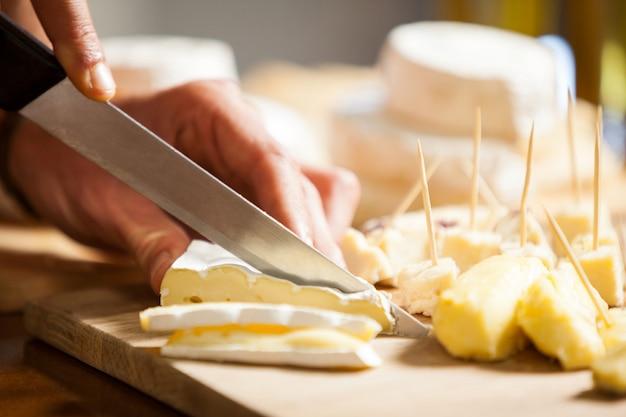 Персонал режет сыр у прилавка на рынке
