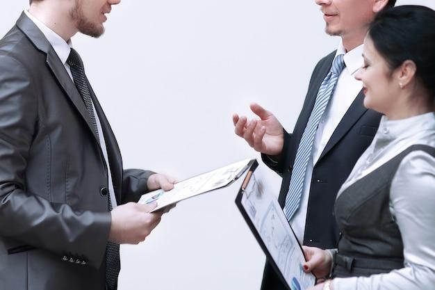 Персонал обсуждает деловые документы, стоя в холле офиса.