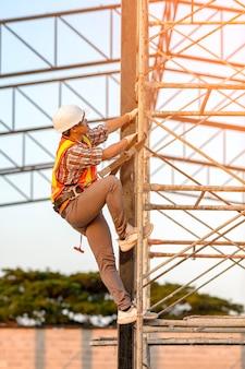 안전 기준에 따라 제복을 입은 직원이 건설 현장에서 작업을보기 위해 비계를 오르고 있습니다.