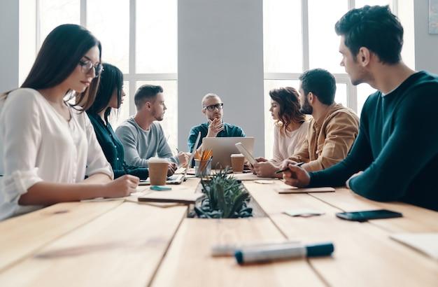 Встреча персонала. группа молодых современных людей в элегантной повседневной одежде обсуждает что-то во время работы в творческом офисе
