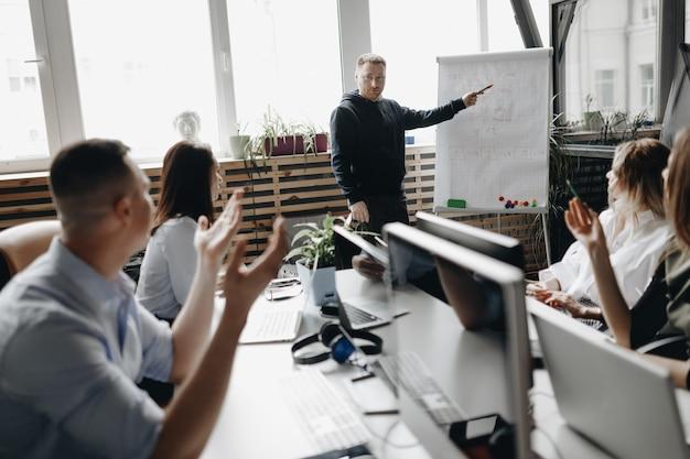 Встреча персонала молодой успешной команды в светлом современном офисе, оснащенном современной оргтехникой
