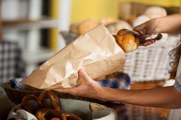 Персонал упаковывает хлеб в бумажный пакет в пекарне