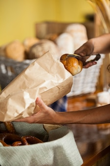 Staff packing bread in paper bag at bakery shop