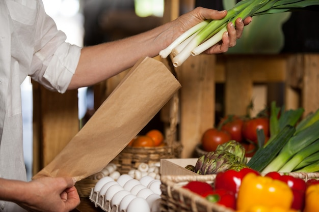 Staff packing spring onion in paper bag at grocery shop