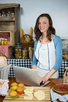 Персонал, использующий ноутбук у прилавка пекарни на рынке