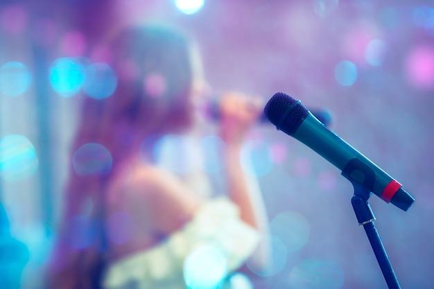 Сценический микрофон на фоне размытой певицы в пятнах синего боке. представление или сольный концерт. современный микрофон и текст караоке ночь на синем фоне