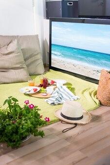Постановочная сцена дома с завтраком и местом для пикника на пледе перед экраном телевизора
