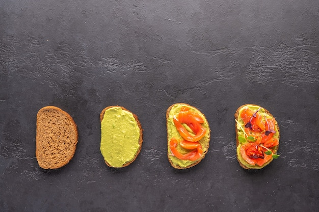 Stages of making a sandwich of bread, guacamole, salted salmon, baked tomatoes and greens