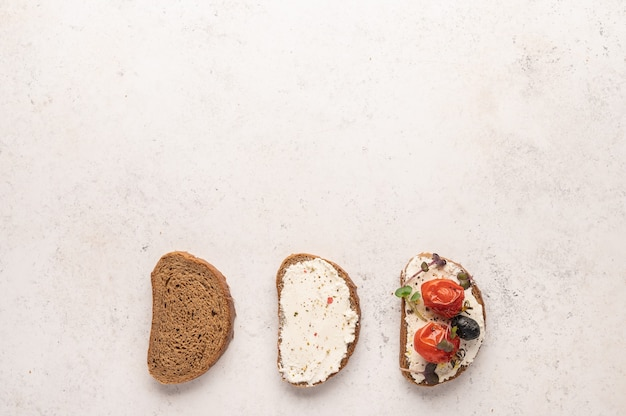 Stages of making a sandwich of bread, ricotta cheese, salted salmon, baked tomatoes and greens on light space