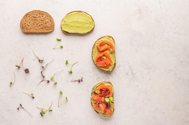 Этапы приготовления бутерброда из хлеба, гуакамоле, малосольной семги, запеченных помидоров и зелени