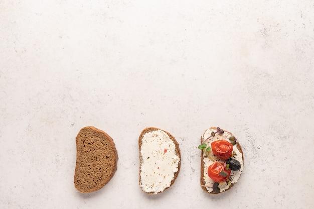 Этапы приготовления бутерброда из хлеба, сыра рикотта, малосольной семги, запеченных помидоров и зелени на светлом пространстве