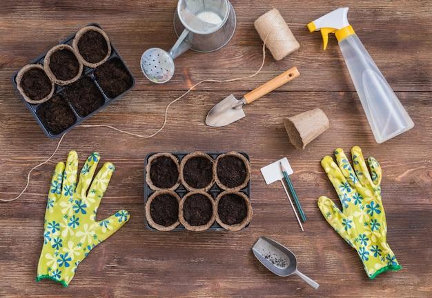 Этапы посадки семян, органические горшки с почвой, садовые инструменты и посуда
