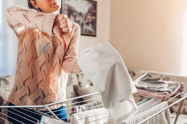 衣服の汚れの汚れ。女性は洗濯後にシャツに斑点を見つけ、親指を示しています