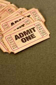 Stained and damaged admission tickets on a mottled brown paper background.